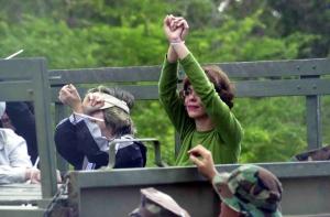 La Vice-Presidenta del PIP, Maria de Lourdes Santiago saluda a la prensa cuando es conducida por policias militares tras ser arrestada en terrenos del Campamento Garcia en Vieques, durante actos de desobediencia civil. Al lado de esta, Maribel Arroyo(Foto por Javier J. Freytes)
